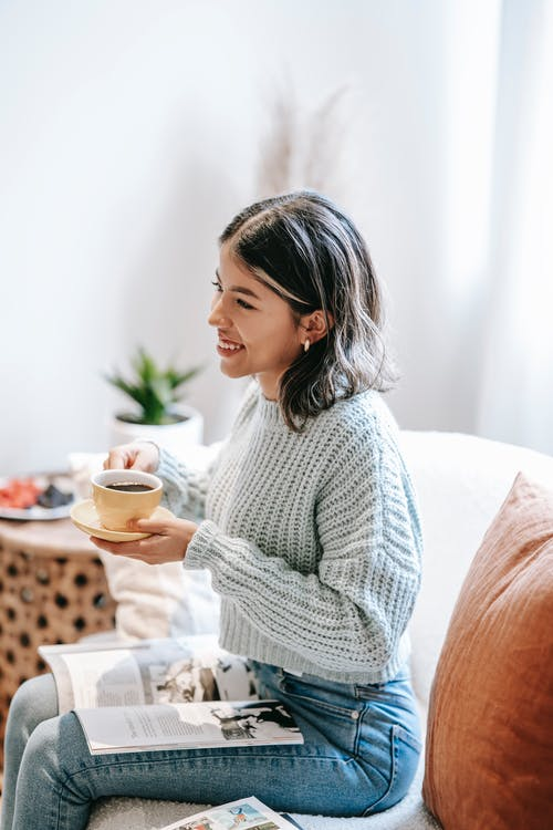 Smiling woman drinking coffee and looking away