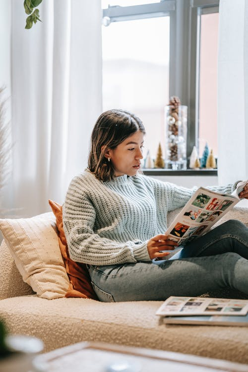 Side view of Asian woman in sweater in jeans reading article in magazine lying on sofa near window