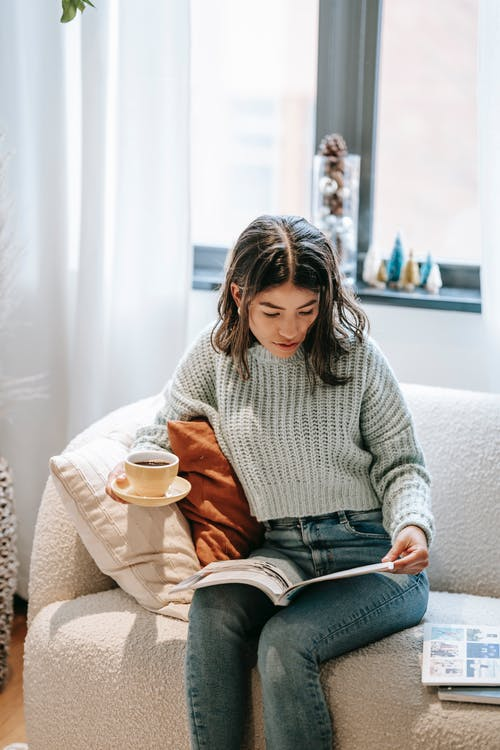 Serious ethnic woman reading magazine sitting with cup of coffee