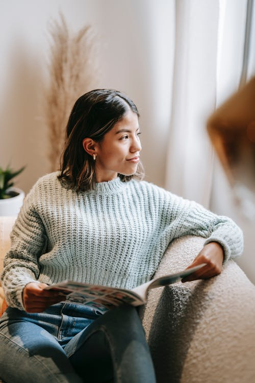 High angle of dreamy Asian female sitting on comfortable sofa and reading magazine while chilling in living room