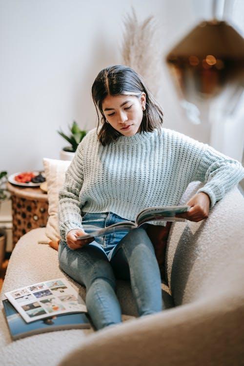 Focused ethnic woman reading article in magazine