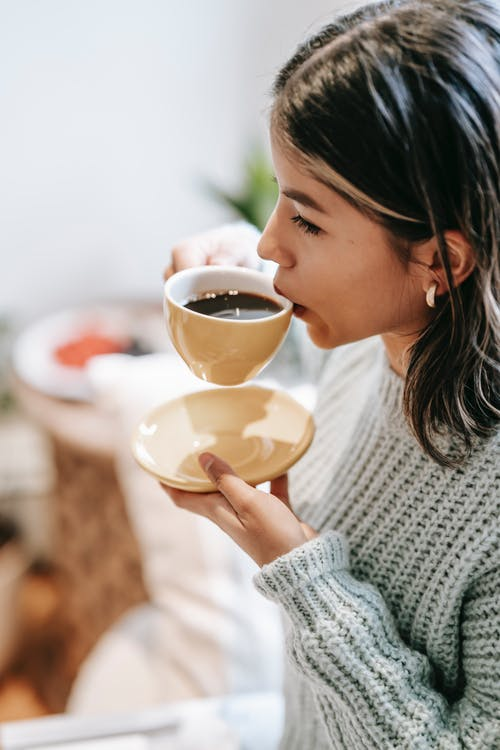 High angle side view of crop Asian female sipping aromatic brewed coffee in mug at home