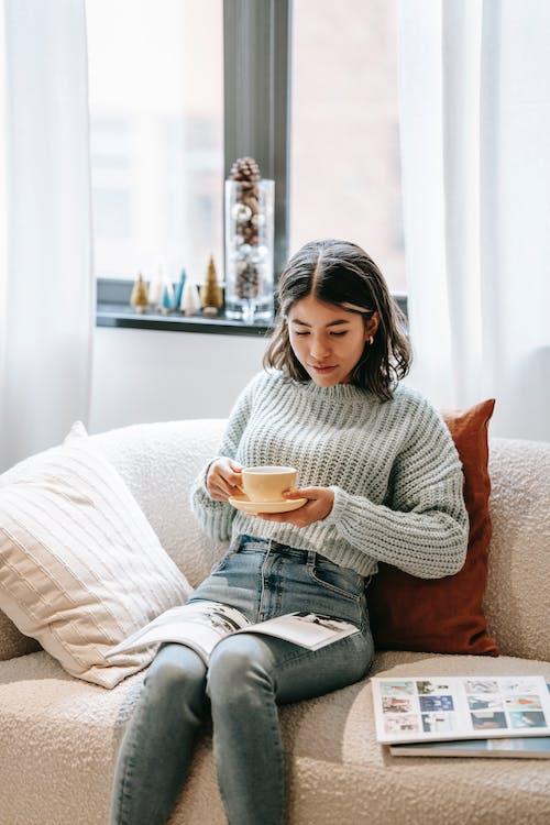 Serious ethnic woman reading magazine on sofa