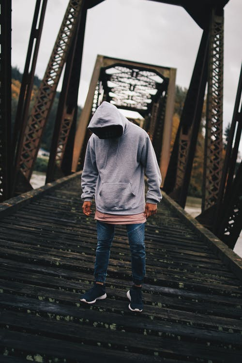 Man in Gray Pull-over Hoodie Standing on Train Rail