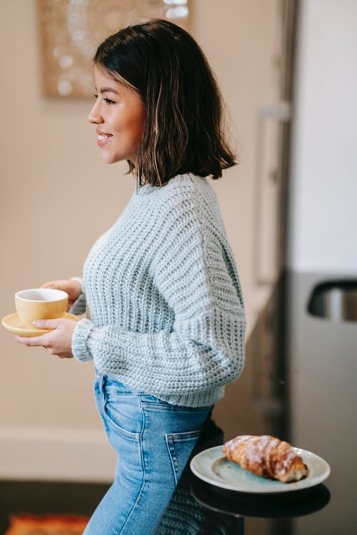 Side view of smiling Asian female with cup of coffee standing near table with delicious croissant