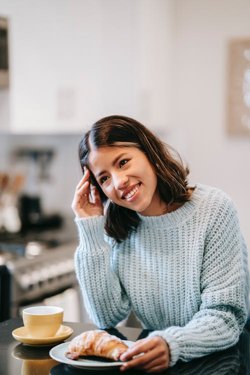 Positive ethnic woman in casual clothes leaning on counter with cup with coffee on saucer and croissant on plate in light kitchen with hand on head looking away