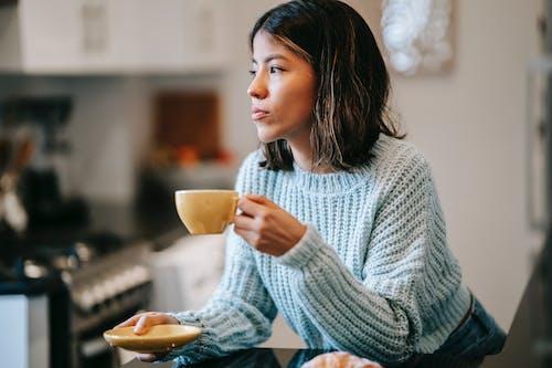Latin American woman near coffee mug and bun in kitchen