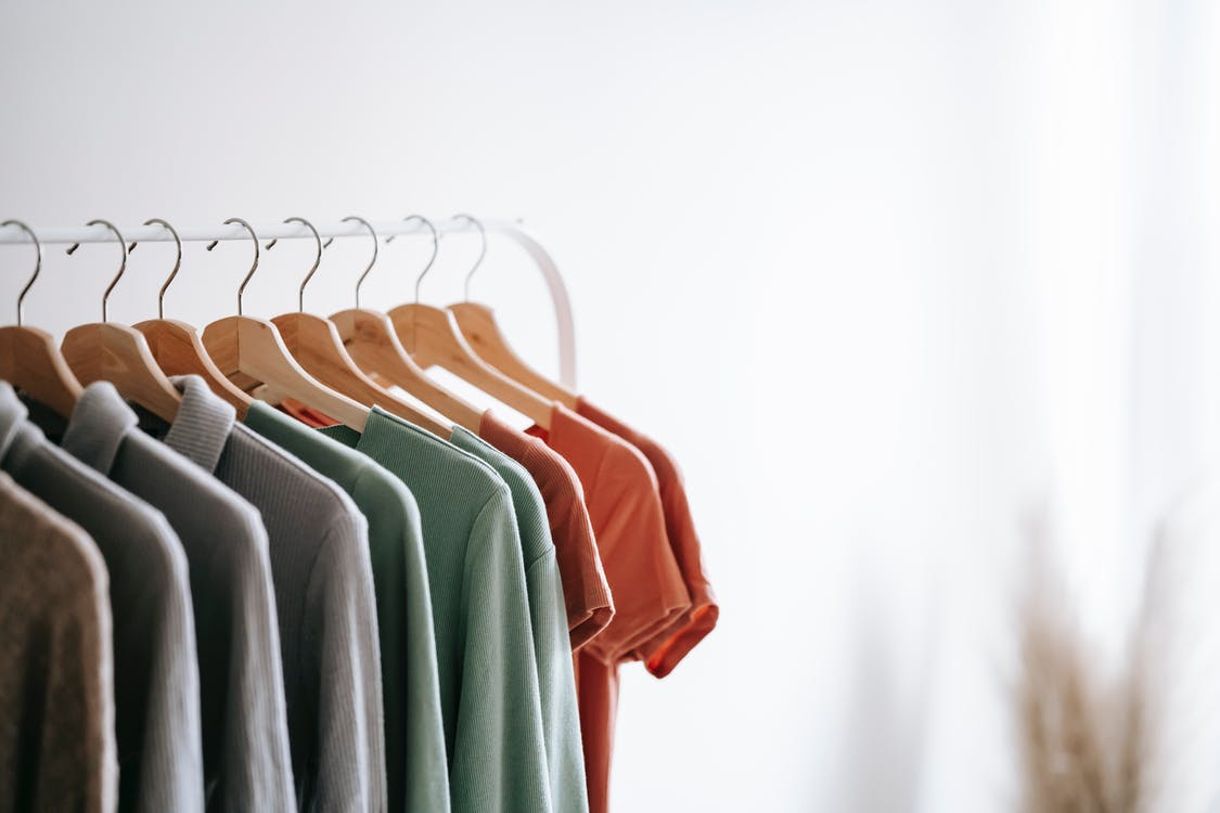 Interior of light apartment with different clothes on wooden hangers in wardrobe near white walls