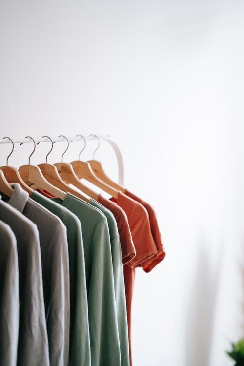 Light room interior with collection of various garments on wooden racks in wardrobe near white walls