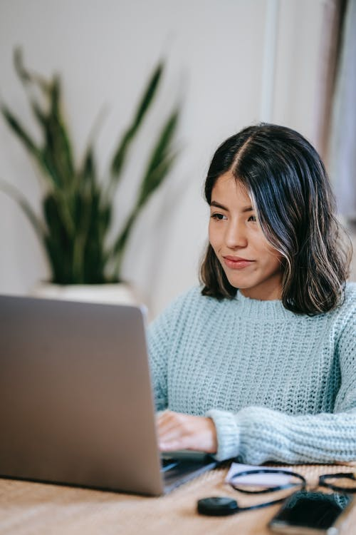 Confident young Hispanic woman in casual clothes working remotely on netbook at table in bright apartment with potted plant with green leaves near wall