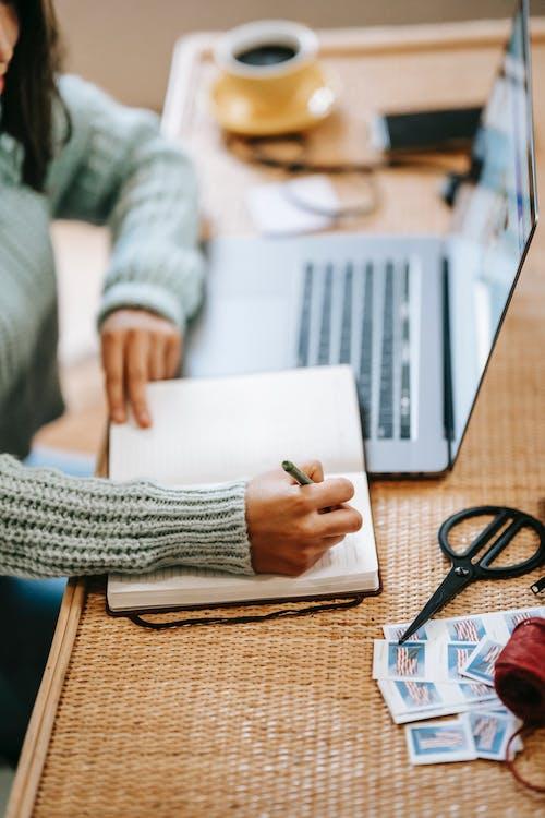 Orang Yang Menulis Di Kertas Putih Di Atas Meja Kayu Coklat