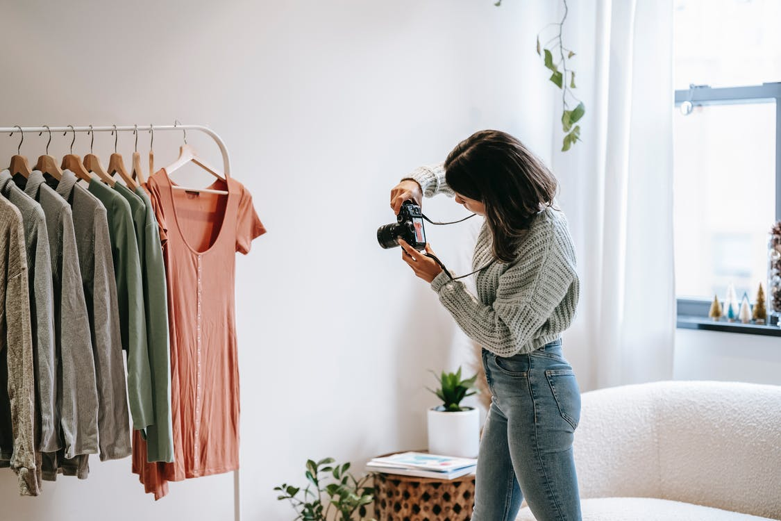 Side view of young female photographer in casual outfit standing in front of hanger and taking picture with camera of shirt in modern apartment
