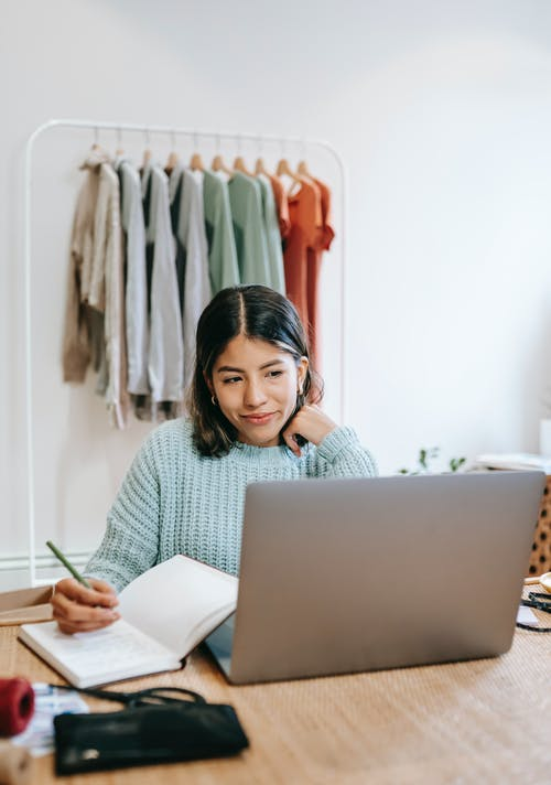 Happy young female freelancer taking notes and working on computer while sitting in front of clothing rack at wooden table in modern apartment