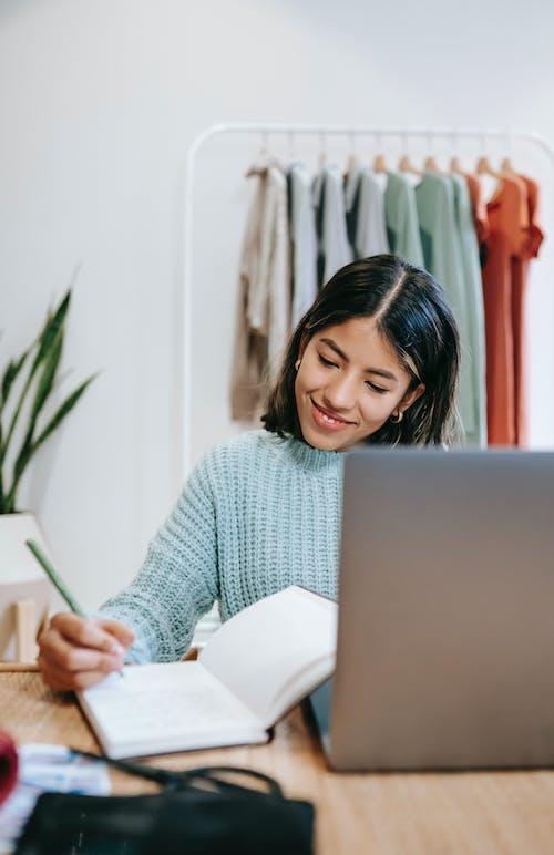 Wanita Dengan Sweater Putih Dan Hitam Menggunakan Macbook Perak