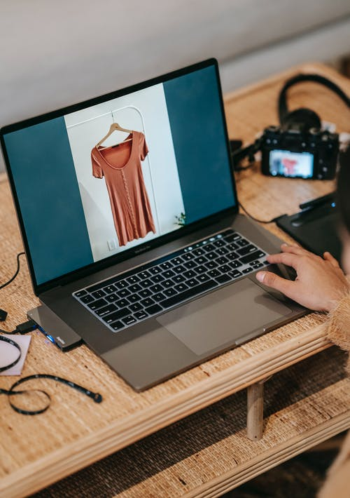 Crop photographer showing photo of blouse on laptop