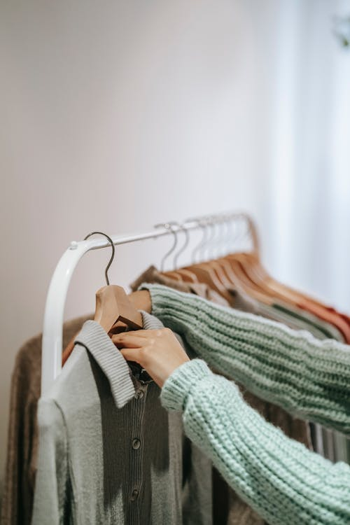Crop unrecognizable female in knitted wear touching wooden hanger with clothes on stand in building
