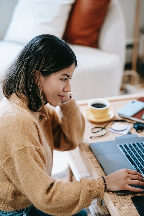 Content ethnic remote employee using laptop at home
