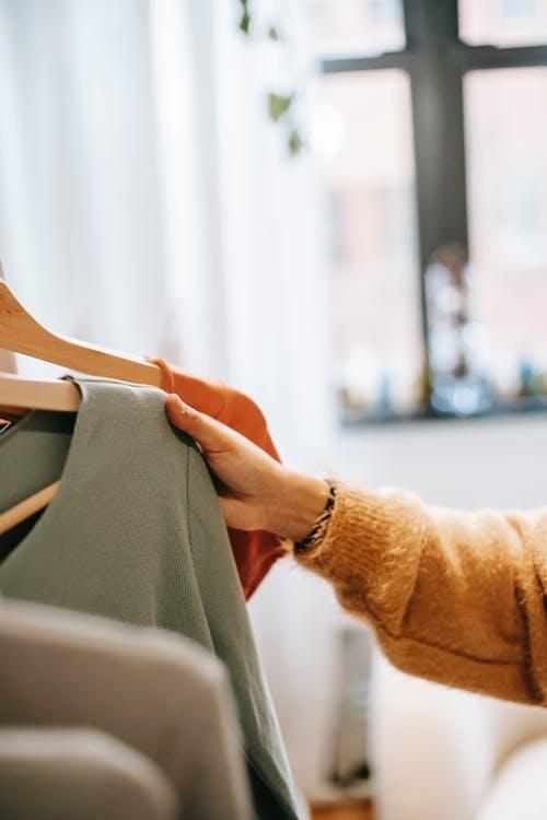 Faceless woman choosing wear in house room
