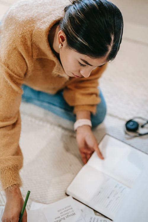 Female with notebook and paper on floor in apartment