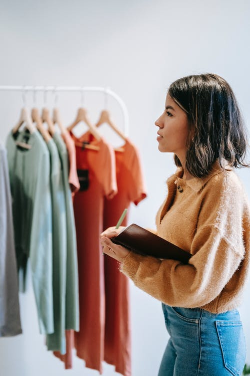 Concentrated lady with notepad near garments on hangers