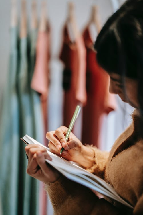 Side view of anonymous lady in casual outfit taking notes in notebook near wardrobe with various multicolored clothes on hangers in light store