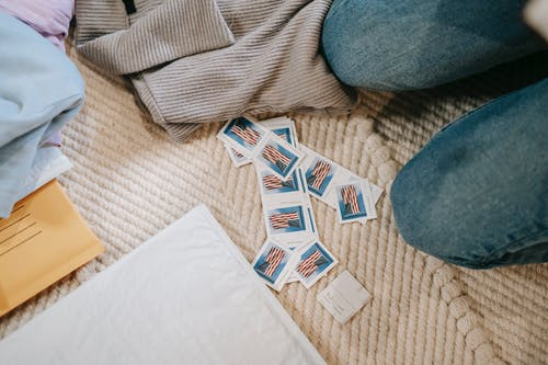 From above crop anonymous person in jeans sitting on carpet on floor near heaped US postage stamps and envelope