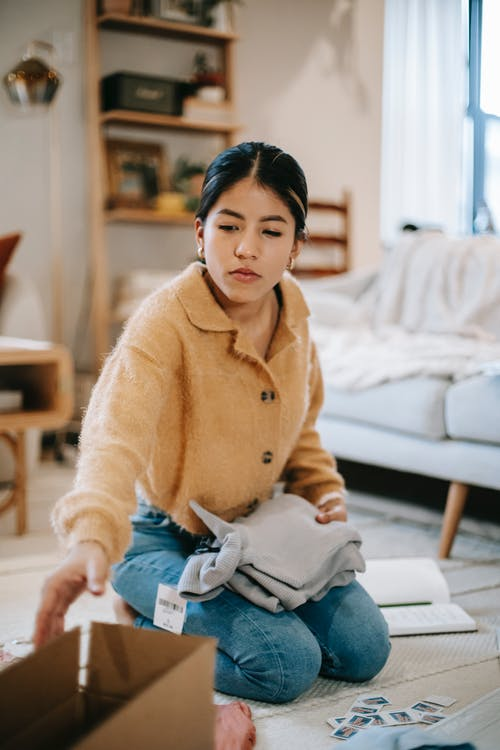 Focused young Asian female wearing casual outfit packing clothes into carton box while sitting on floor in modern living room