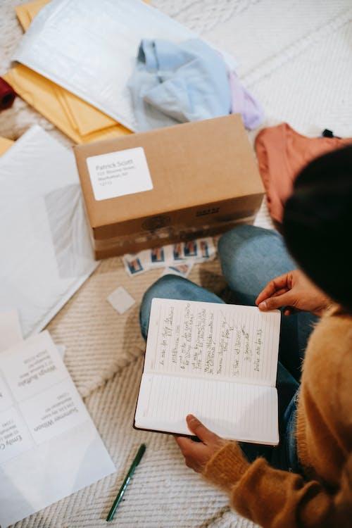 Crop unrecognizable woman preparing carton box for sending