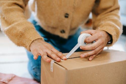Crop unrecognizable woman sealing carton parcel with tape