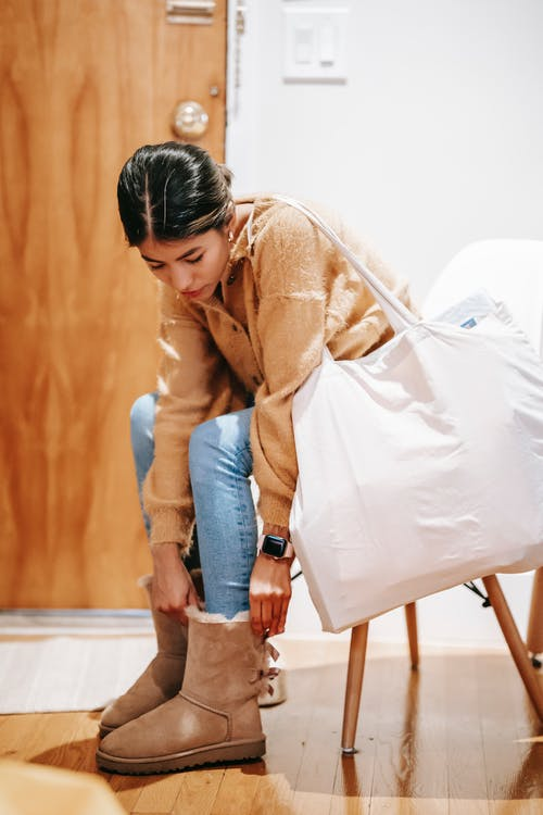 Focused young Asian female in jeans and warm sweater sitting on chair with big bag and putting on winter boots in light entrance hallway