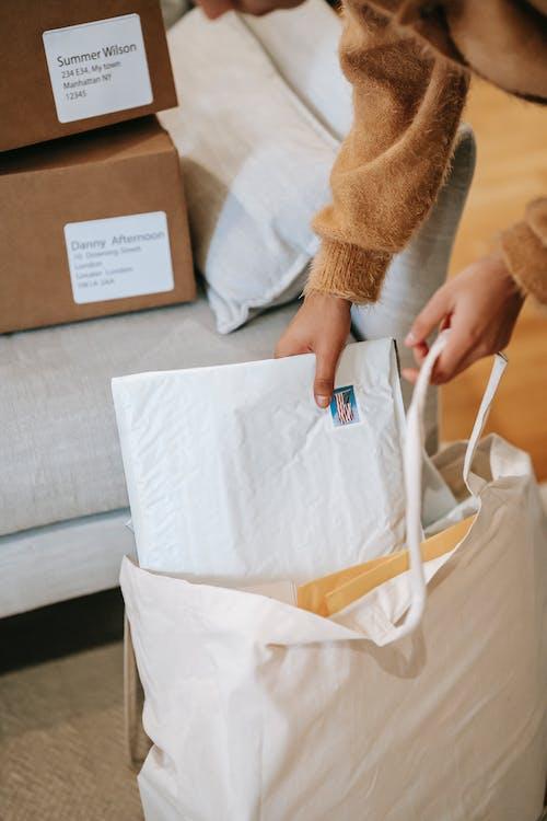 Crop faceless woman putting parcels into big bag