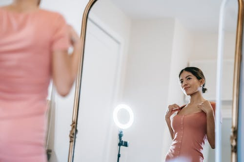 Attractive woman looking in mirror against ring lamp
