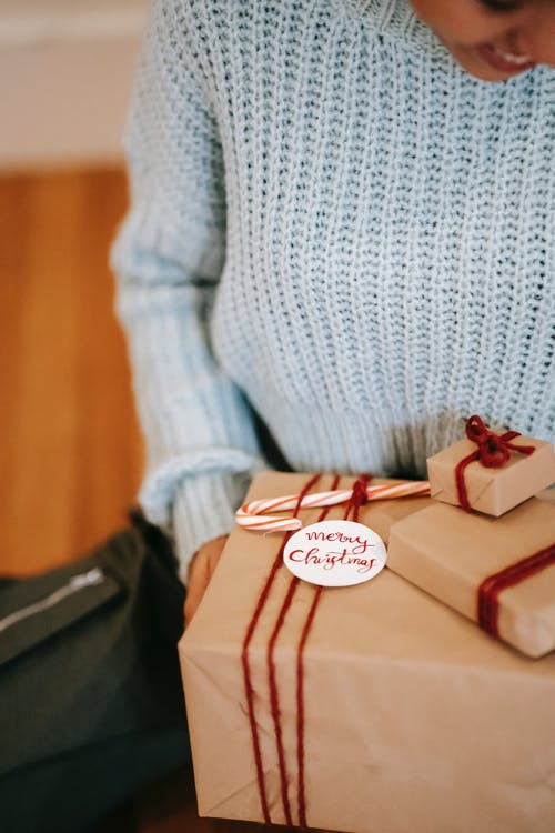 Crop happy female in blue sweater sitting on floor with wrapped present boxes during festive season