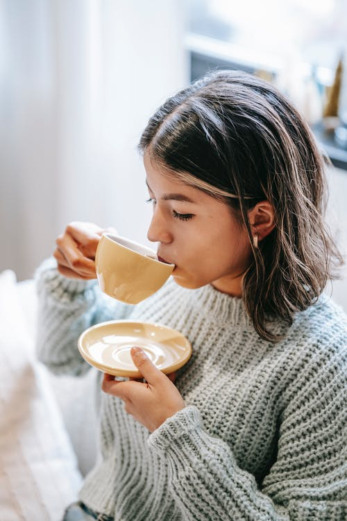 Positive young female in knitted sweater drinking freshly brewed hot coffee in light living room