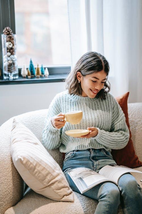 Smiling Asian woman reading magazine and enjoying hot coffee