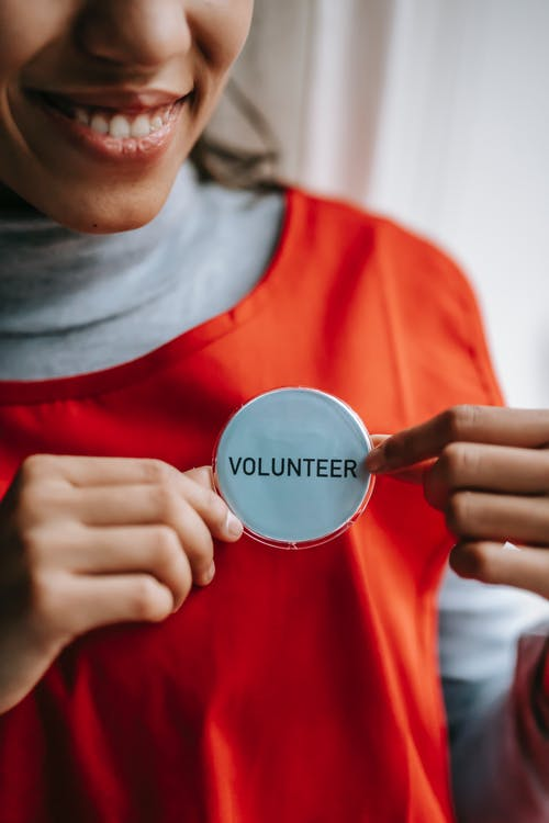 Smiling ethnic woman showing volunteer sign on red apron