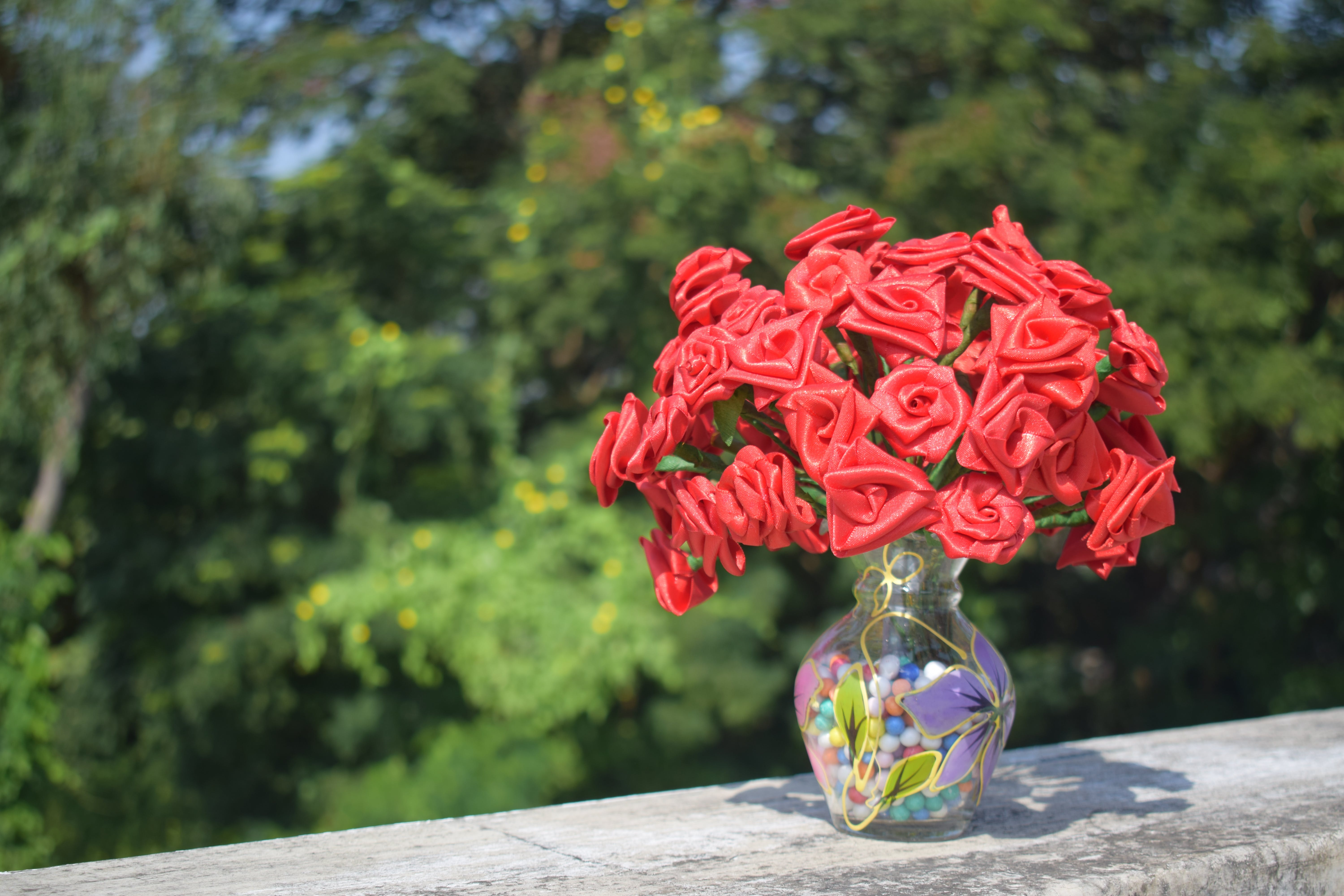 Artificial Roses in Clear Glass Vase on Concrete Surface