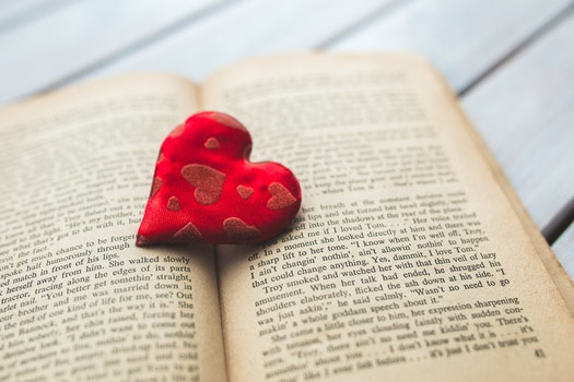 Red heart on a old opened book