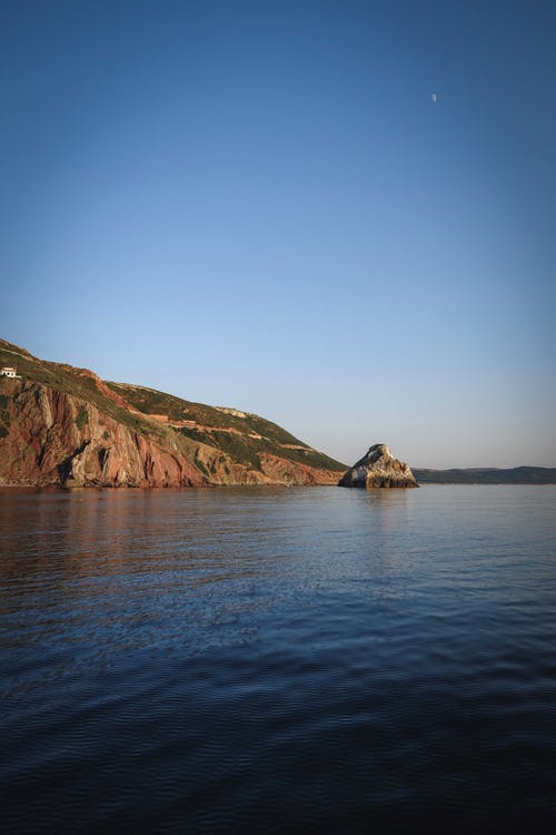 Scenic landscape of rocky cliff located in calm sea water under cloudless blue sky