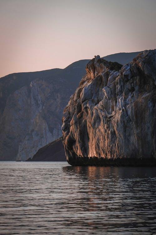 Rocky cliffs surrounding rippling sea at sunset