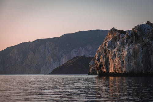 Rocky mountains near rippling sea at sundown