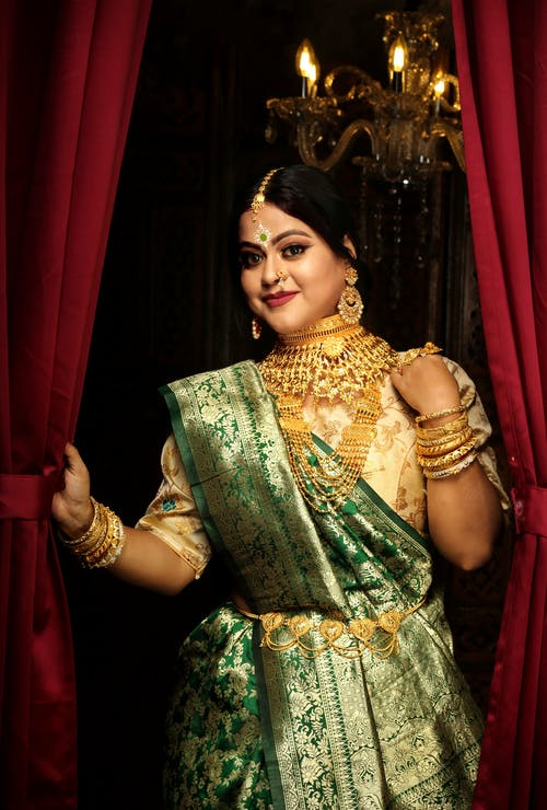 Woman in Green and Gold Sari Dress Holding Silver Container