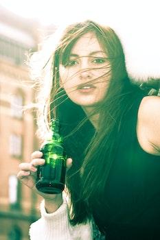 Woman In Black Sleeveless Shirt Holding A Bottle