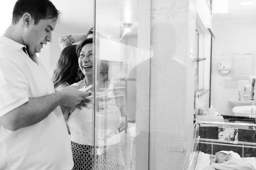 Black and white of delighted grandmother and father with smartphone standing near sleeping newborn child in maternity hospital