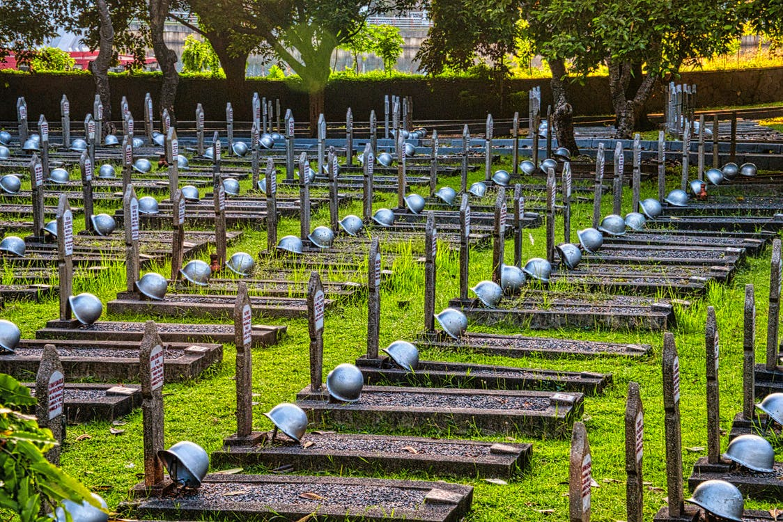 Tombstones with military hardhats located on grassy ground near tall green tall trees in national main heroes cemetery in Indonesia