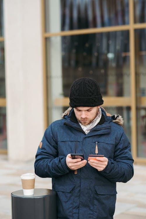 Uomo In Berretto Nero E Giacca Blu Che Tiene Smartphone
