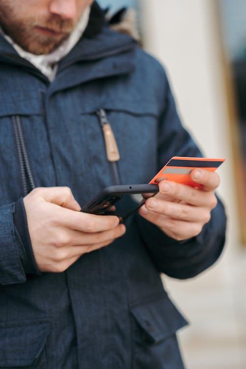 Person in Black Denim Jacket Holding Black Smartphone