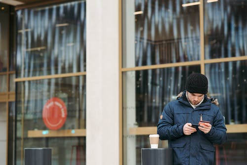 Focused young male in warm outerwear and hat standing near modern building with takeaway coffee and using smartphone while making online shopping with credit card
