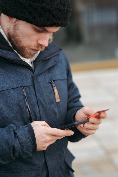 Uomo In Giacca Di Jeans Blu Che Tiene Smartphone Nero
