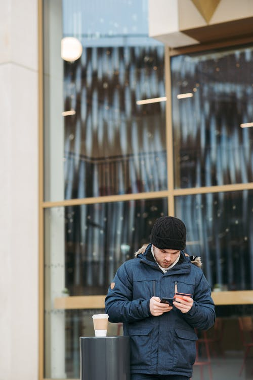 Man in Black Knit Cap and Blue Jacket Holding Black Smartphone